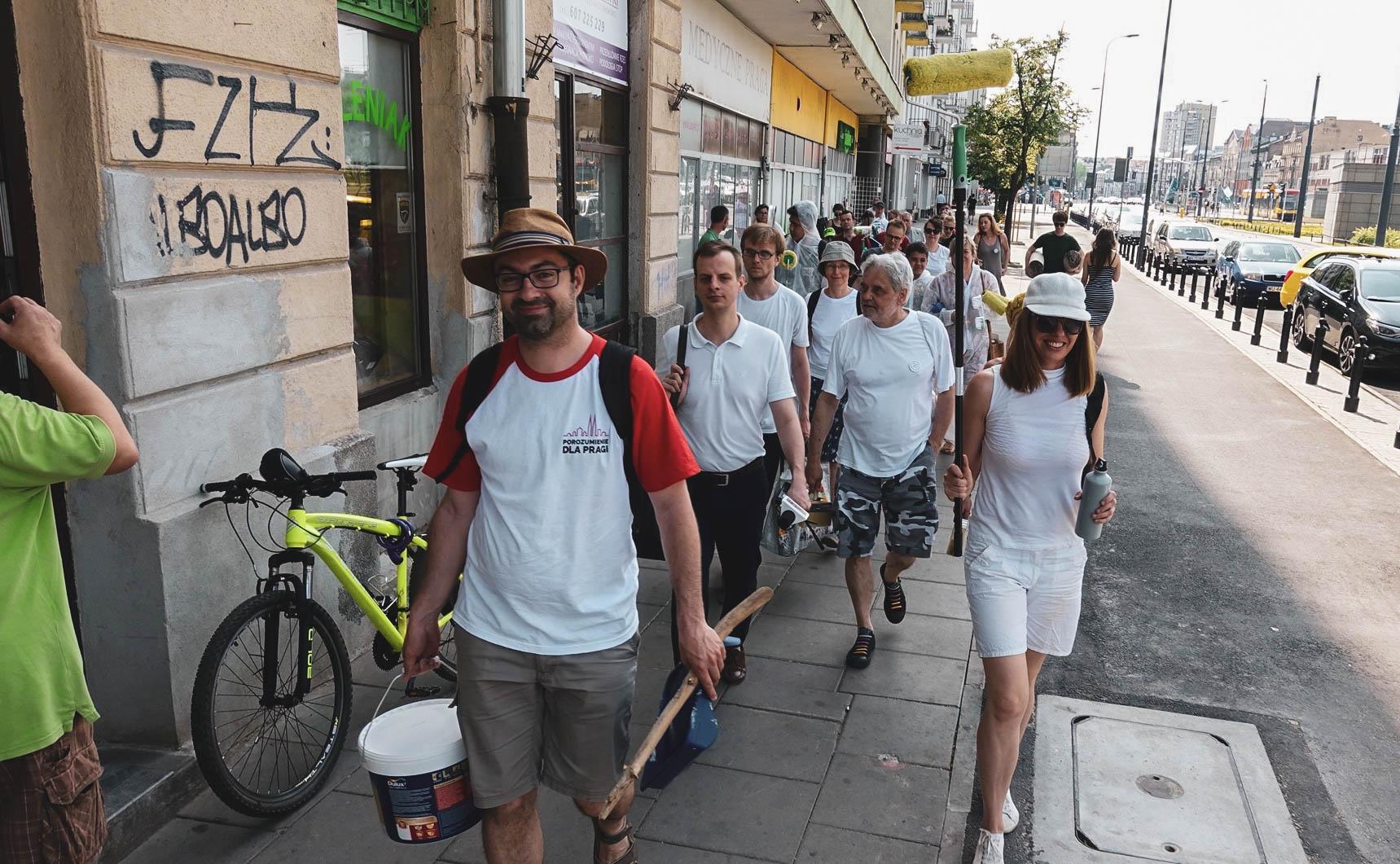 Ekipa Porozumienia dla Pragi idzie ul. Targową trzymając w dłoniach kubły z farbą, wałki, pędzle itd.